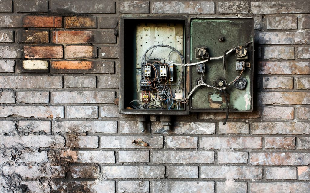 Older electrical panel on brick wall