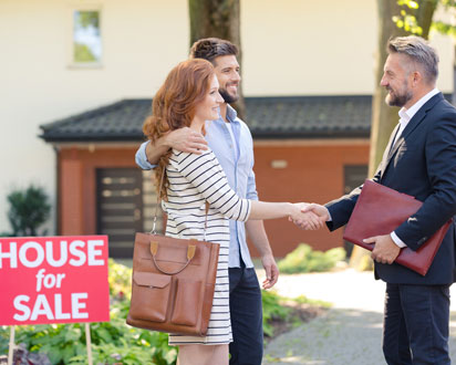 Real estate agent shaking hands with a couple in front of a house for sale.