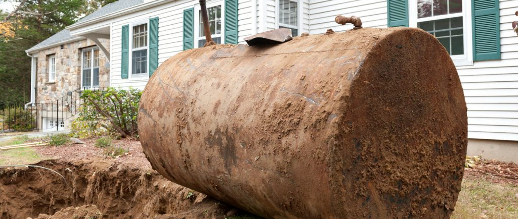Underground oil tank being removed from ground in front of home