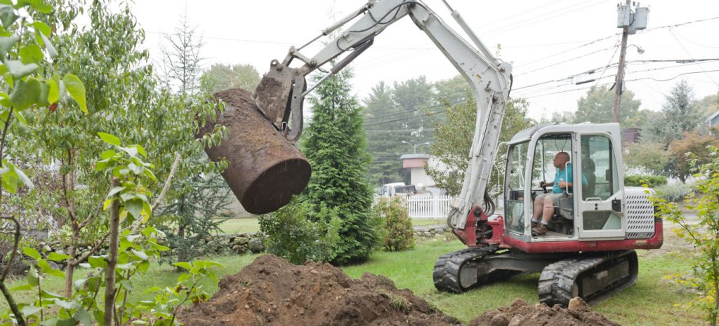 A man uses a compact excavator to remove an old, rusty underground oil tank from a residential yard.