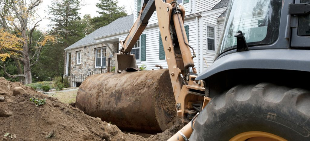 Excavator removing an underground oil tank
